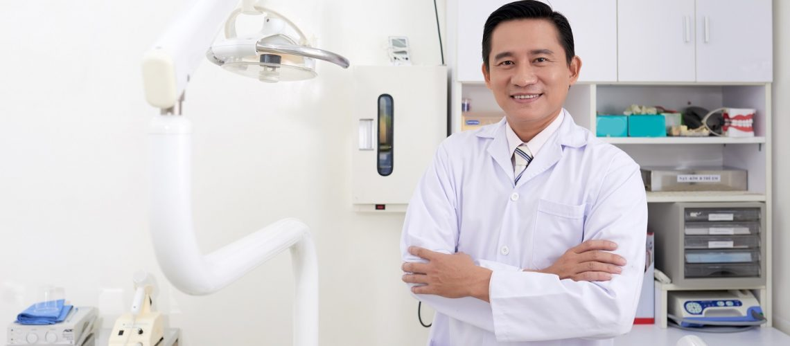Cheerful Asian dentist standing in his office with his arms crossed