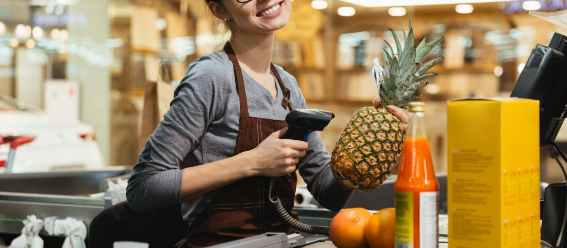 happy-female-cashier-scanning-grocery-items (Copy)
